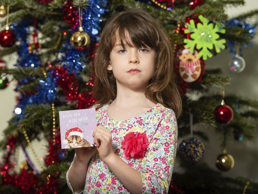 Florence Widdicombe, 6, poses with a Christmas card from the same pack as a card she found containing a message apparently from foreign prisoners in China. The U.K.-based grocery chain Tesco has halted production at the factory in China that supplied the cards.