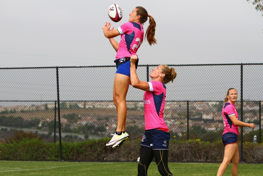 "Lauren Doyle is lifted up for a catch by teammate Carmen Farmer during practice. The Olympics will feature a seven-on-seven game, in contrast to traditional rugby that can feature 13 (""league"") or 15 (""union"") players per side."