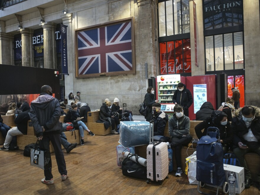Passengers wearing face masks wait next to the Eurostar Terminal at Gare du Nord train station in Paris on Monday. France is banning all travel from the U.K. for 48 hours in an attempt to make sure that a new strain of the coronavirus in Britain doesn't reach its shores.