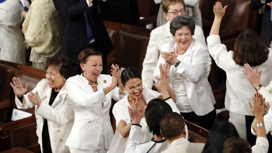 Women of Congress, including Rep. Alexandria Ocasio-Cortez, D-N.Y. (center), cheer after President Trump acknowledges their increased numbers in Congress, during his State of the Union speech.