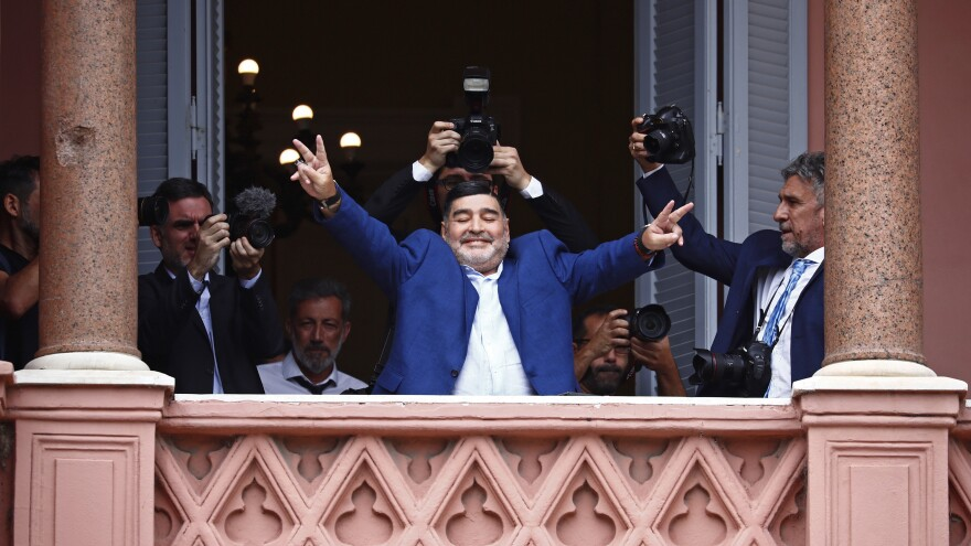 Soccer great Diego Maradona flashes victory signs to fans below at the Casa Rosada government house in Buenos Aires after meeting with Argentina's president last December. Maradona died Wednesday at age 60.