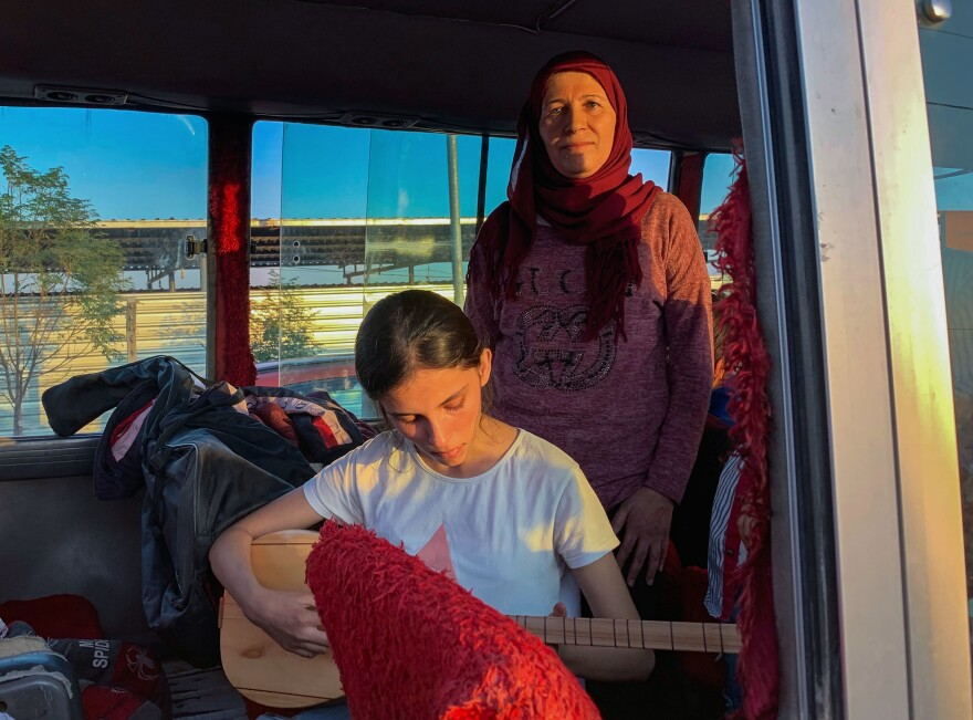 """We brought our ambitions,"" says Najah Raso. She and her daughter, Solin, 14, holding a Kurdish lute, were on a bus of refugees arriving from the Syrian border to a camp in the Kurdistan region of Iraq this week. More than 2,000 people arrived in Iraq over a six-day period, fleeing Turkey's assault on northeastern Syria."
