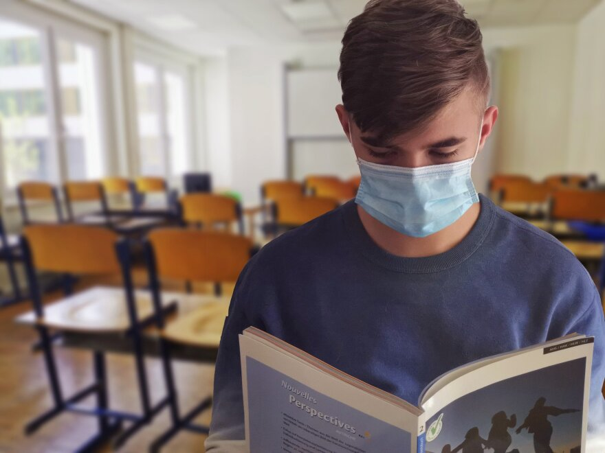 A picture of a student reading a book in a classroom.