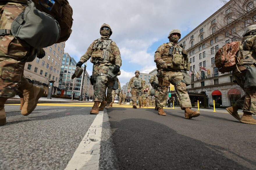 Members of the National Guard walking through Black Lives Matter Plaza to switch shifts with other members after President Biden inauguration ceremony ended in Washington D.C.