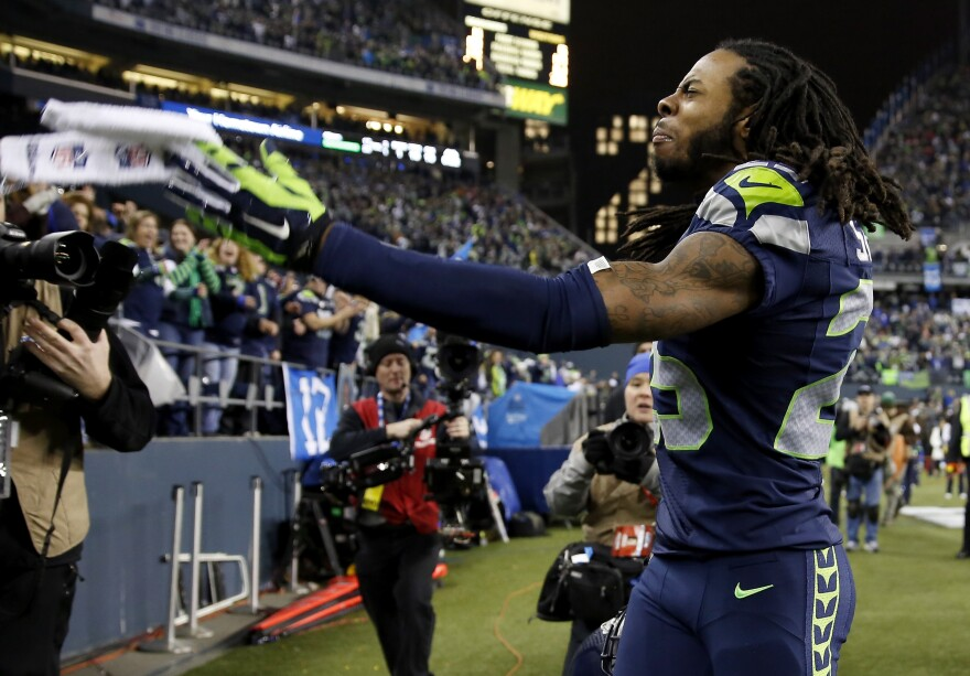 Seattle Seahawks cornerback Richard Sherman has been fined by the NFL for unsportsmanlike behavior after his team's win over San Francisco in the NFC title game. He's seen here on the sideline after tipping a pass that led to a game-clinching interception.