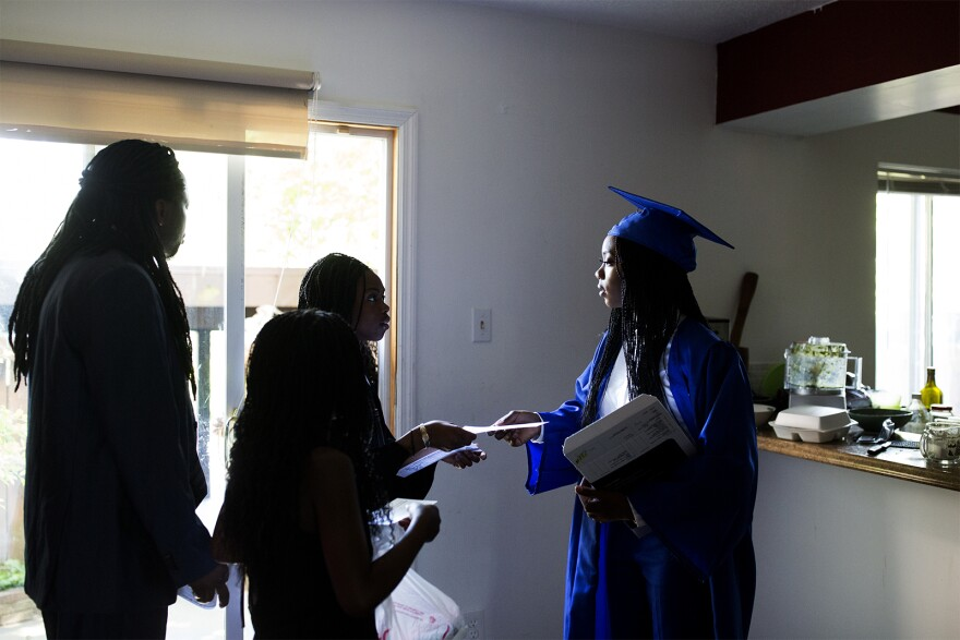Ngone hands out graduation tickets to her father and sisters as they leave for the ceremony.
