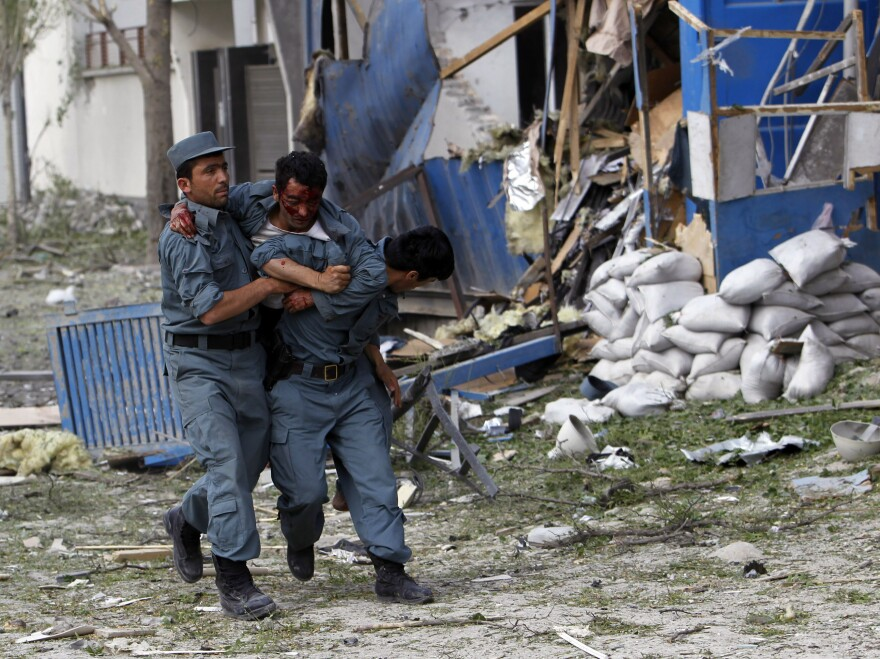 A wounded Afghan police officer is helped from the scene of Friday's explosion and gunfire in Kabul.