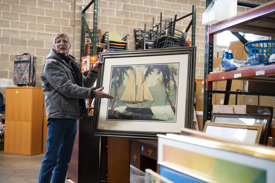 George Hayes lifts a painting to show his wife Mary at the Home Sweet Home furniture bank. Feb