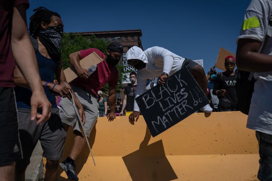A demonstrator hops over a barrier near the St. Louis Metropolitan Police headquarters Sunday, June 7, 2020.