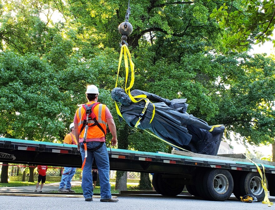 Crews lower the statue of Christopher Columbus onto a flatbed trailer on June 16, 2020.