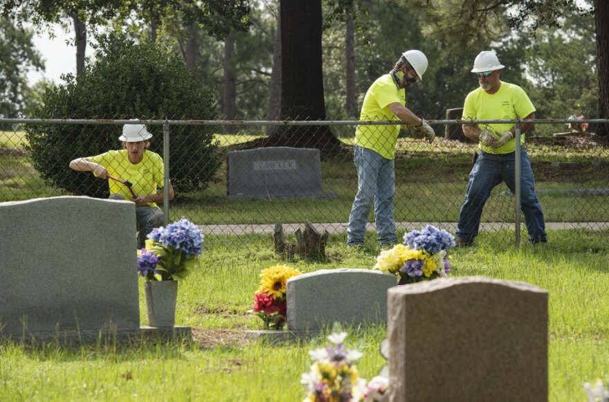 JC Brown, Skipper Hortman and Mark Hooks of Mineola Public Works work to remove the fence between the segregated Black burial area at Cedars Memorial Gardens Cemetery, formerly Mineola City Cemetery on  July 15 in Mineola.