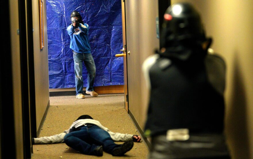 """A student (R) engages a gunman overa mock shooting victim during a Tac*One Consulting """"Lone Wolf"""" civilian active shooter response course for concealed weapons permit holders in Longmont, Colorado."""