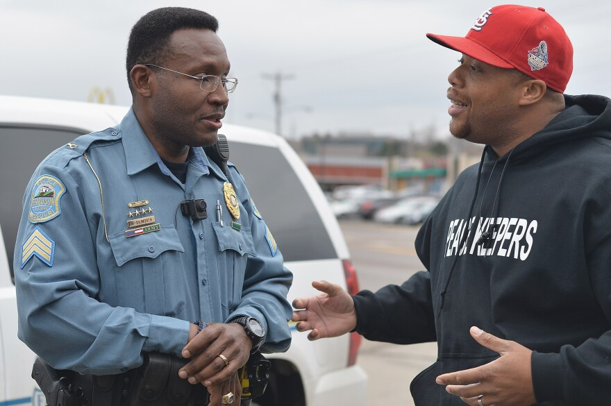 Sergeant Harry Dilworth of the Ferguson Police Department speaks with local citizen and peacekeeper Paul Muhammed in Ferguson, Mo., Saturday. The St. Louis suburb is anticipating a ruling from a grand jury in the police shooting of Michael Brown.