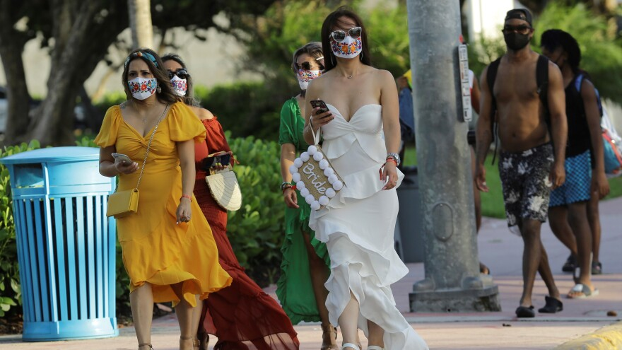 People wearing protective face masks walk along Ocean Drive during the coronavirus pandemic, Friday, July 24, 2020, in Miami Beach.