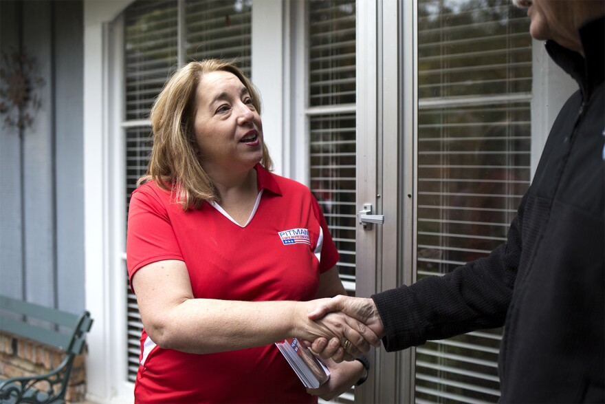 Lee Ann Pitman greets a resident of the 99th district while knocking on doors on Friday afternoon. Oct. 25, 2019