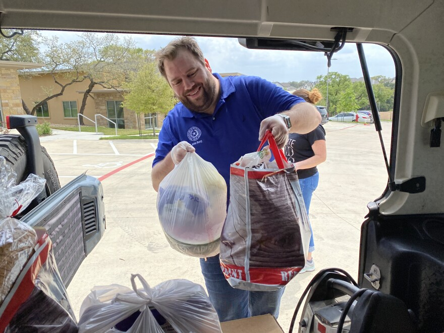 Rep. John Bucy loads a car with donated food to be delivered to households in need in House District 136.