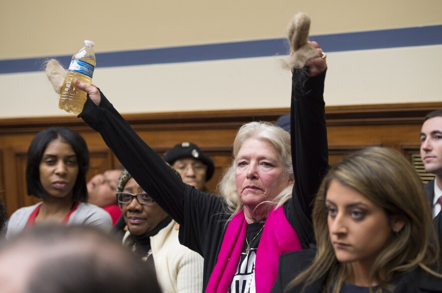 Flint resident Glaydes Williamson holds up a bottle of water from the city and hair pulled from her drain during a House Oversight and Government Reform Committee hearing in Washington, D.C., in February.
