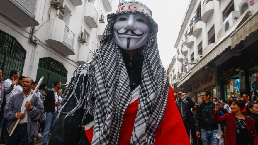 """<strong><a href=""""http://menasolidaritynetwork.com/2012/05/02/tunisia-thousands-fill-streets-to-celebrate-may-day/"""">Tunis, Tunisia</a>:</strong> A man wears an Anonymous mask during a May Day rally on May 1."""