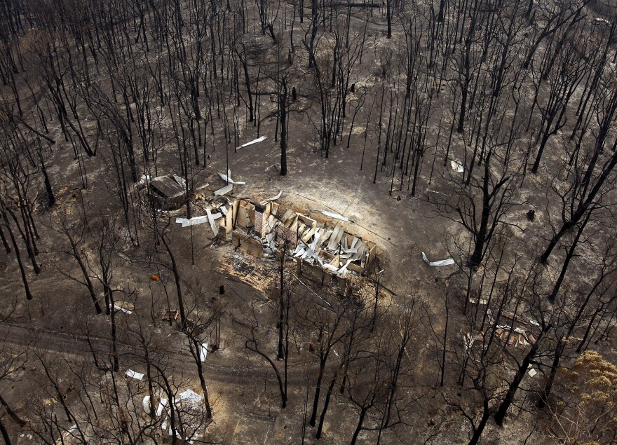 Following the catastrophic bushfires in 2009, the burned remains of a house sit among charred trees near the town of Kinglake in Australia.