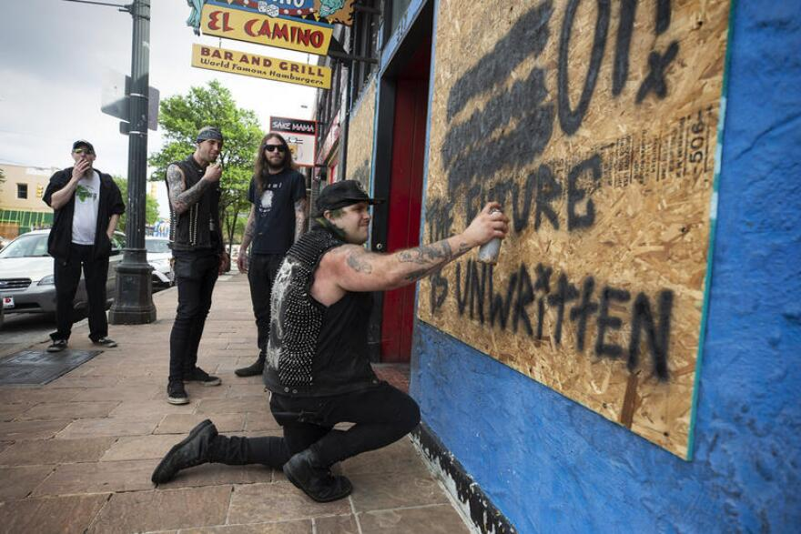 Zach Volta, chef at Casino El Camino, spray paints the boarded-up window on the front of the Sixth Street restaurant as his coworkers watch.