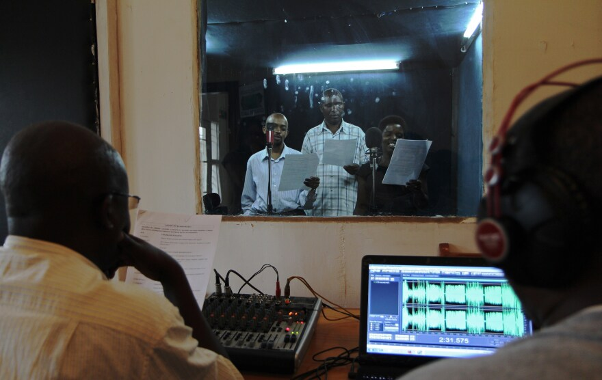 """Actors reading during the recording of an episode of the radio soap opera """"Musekeweya"""" in Kigali, produced by the NGO <a href=""""http://www.labenevolencija.org/"""">Radio La Benevolencija.</a> Twice a week, people all around Rwanda gather in groups to listen together."""
