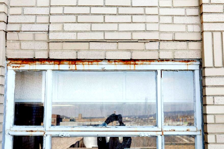 This image from before work began shows rusted window frames and failing brick work prevalent around the building.