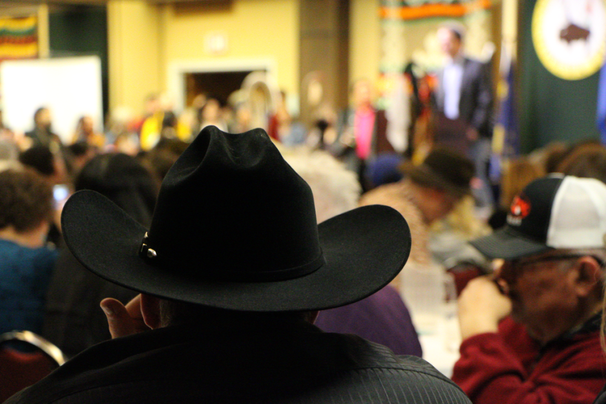 A man in a black cowboy hat looks towards the center of a crowded room.
