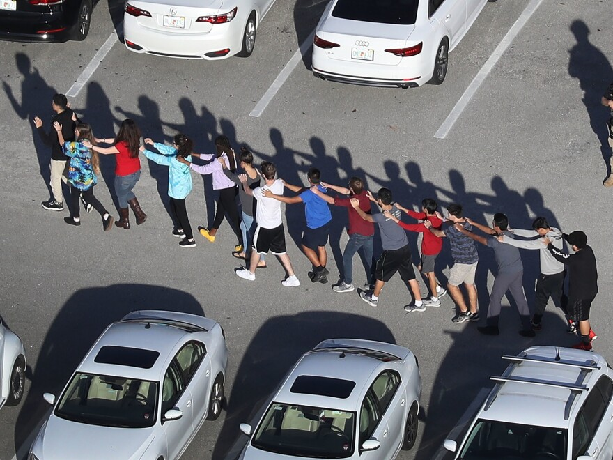 People are brought out of the Marjory Stoneman Douglas High School after a shooting at the school that killed and injured multiple people on Wednesday in Parkland, Fla.