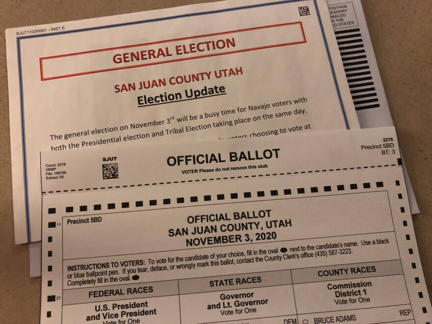 """An envelope that says General Election, San Juan County Utah in the background. A paper that says """"official ballot"""" in the foreground."""