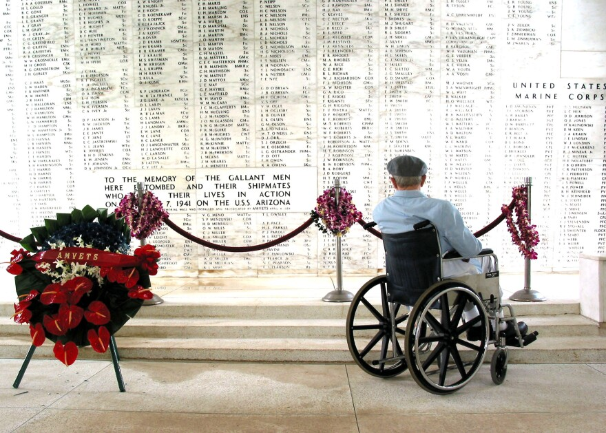 Pearl Harbor survivor Bill Johnson reads the list of names inscribed in the USS Arizona Memorial.