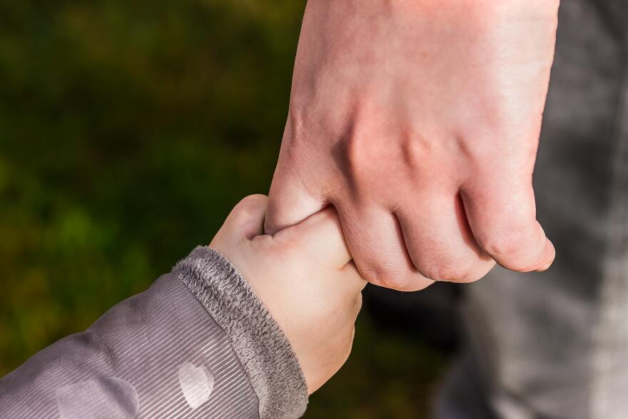 tiny baby hand clutches the index finger of an adult.