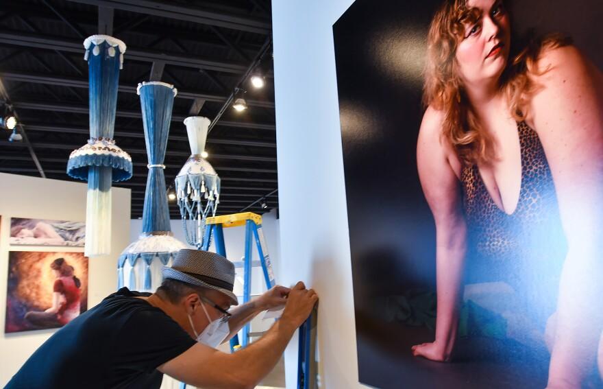 Michael Schonhoff affixes an exhibition label to the BFA exhibit.