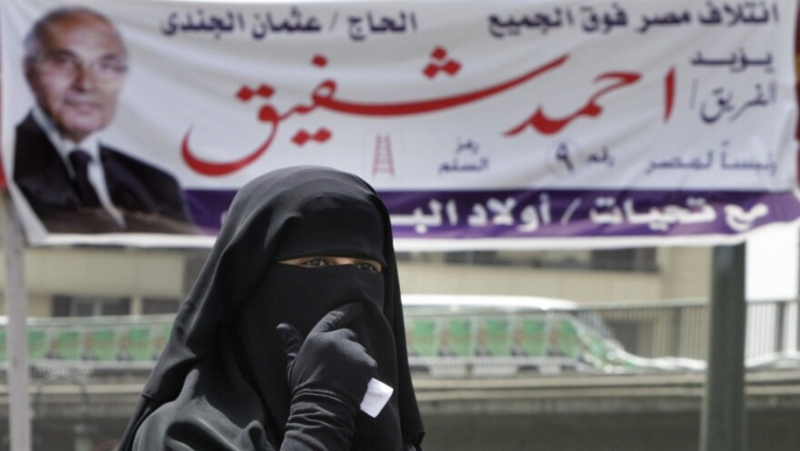 An Egyptian woman walks under a campaign banner in Cairo on Tuesday. Egypt holds its first competitive presidential election on Wednesday and Thursday, with a dozen candidates in the race.