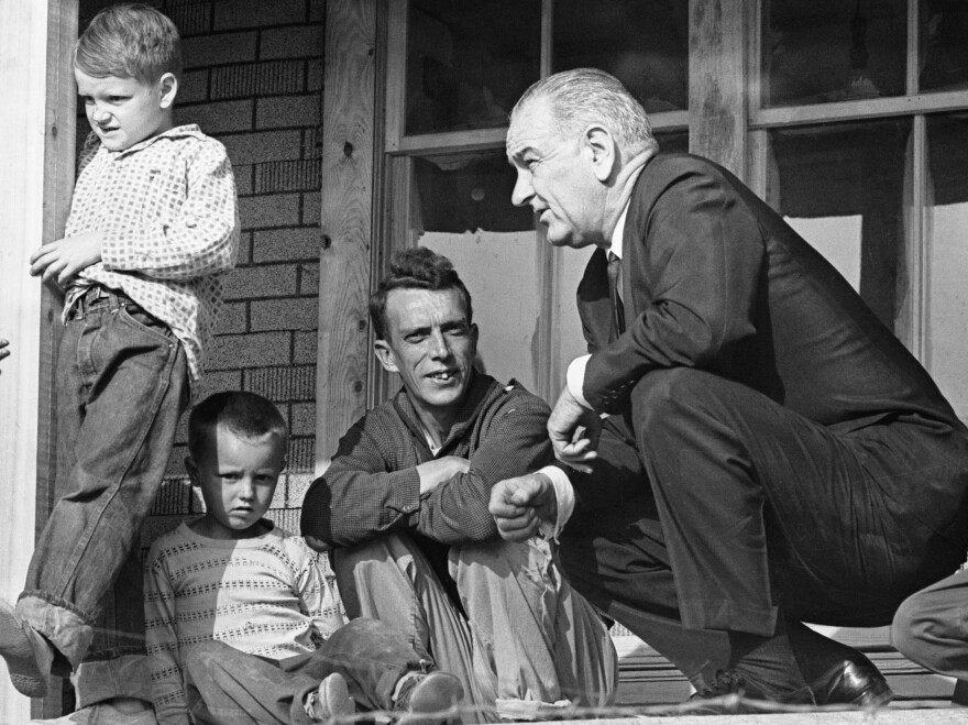 President Lyndon Johnson, on the porch of Tom Fletcher's cabin, listens to Fletcher describe some of the problems in Martin County, Ky., in 1964.