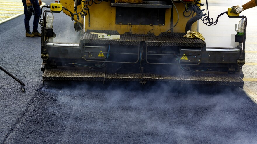 Photo of a machine and workers laying asphalt on a road