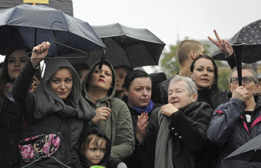 Massive protests were held in the rain in the streets of Warsaw, Gdansk, Wroclaw and elsewhere across the largely Catholic nation of Poland, as the conservative-controlled legislature considers an absolute ban on abortion. Here, women in Warsaw hold up a coat hanger, a symbol of dangerous and illegal abortions.