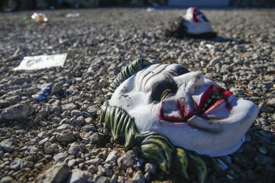 Halloween masks litter the ground amongst signs of chaos at the scene where a deadly shooting in Greenville, Texas, Sunday, Oct. 27, 2019.