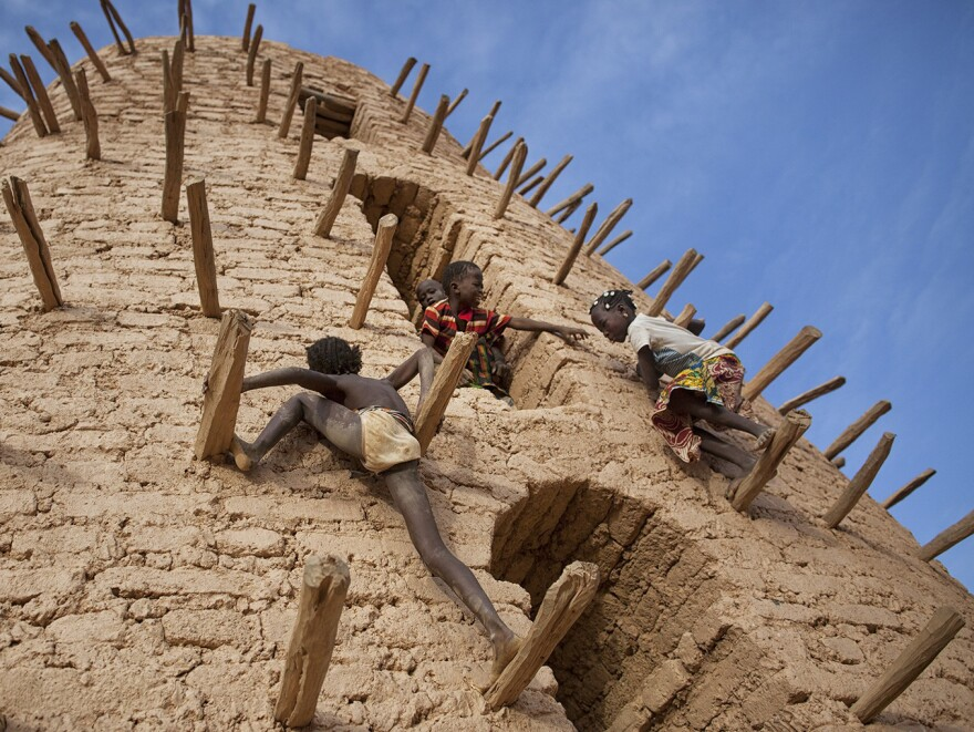 """Friends play on the main minaret of the Grand Mosque in Bani, Burkina Faso, during the Muslim holiday<strong> </strong><a href=""""http://hereandnow.wbur.org/2015/07/17/muslim-call-to-prayer"""">Eid al-Fitr.</a>"""