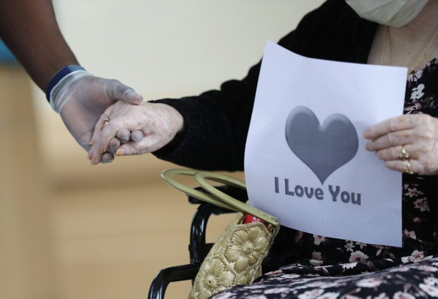 A nursing home worker holds the hand of an elderly lady in a wheelchair.