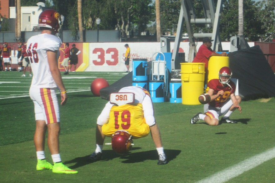 Jake Olson, in the yellow jersey, snaps the football on the USC practice field. The 18-year-old lost his sight at age 12, and now is a walk-on reserve long snapper for the USC Trojans.