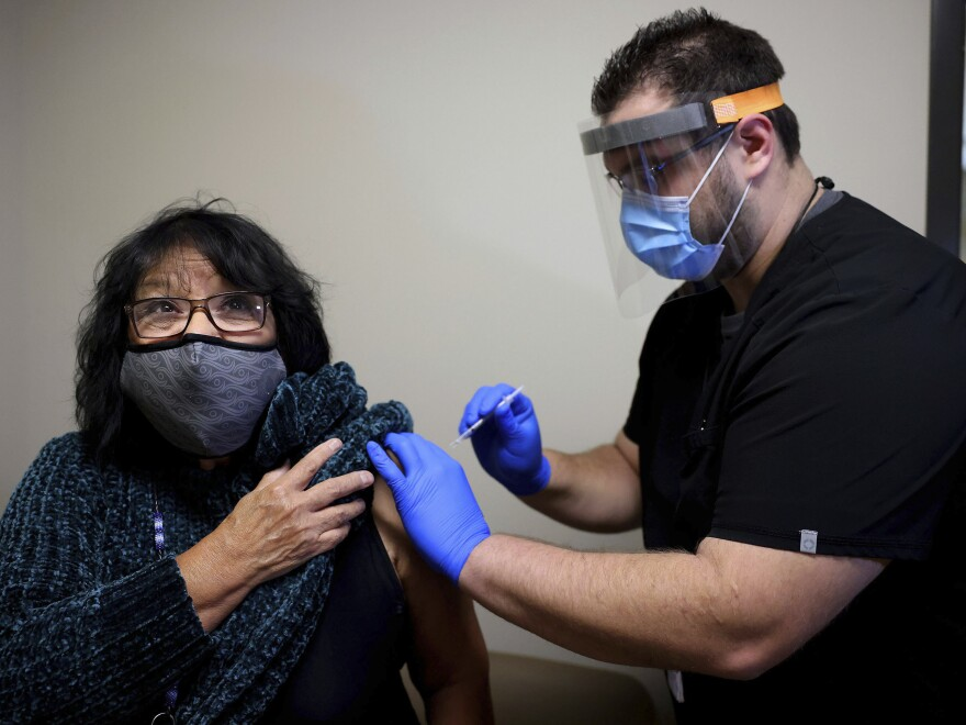 Meda Nix, a citizen of the Cherokee Nation and a Cherokee language speaker, receives a COVID-19 vaccine from Dr. Matthew Reece at the Cherokee Nation Outpatient Health Center Thursday, Dec. 17, 2020, in Tahlequah, Okla.