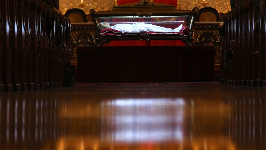 The remains of St. Maria Goretti lie near the altar during Mass at St. John Cantius Church in Chicago on Oct. 12. It was one of 54 churches where her body was exhibited during a U.S. tour.