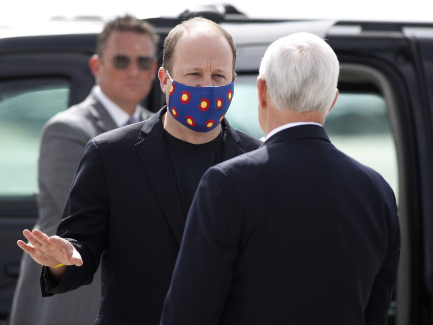 Colorado Gov. Jared Polis wears a mask with the state's flag as he greets Pence in Colorado Springs.