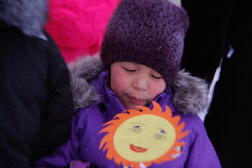 Julianne Kuko, 9, holds a drawing of the sun as she and her classmates perform a song to welcome the first sunrise in 58 days.
