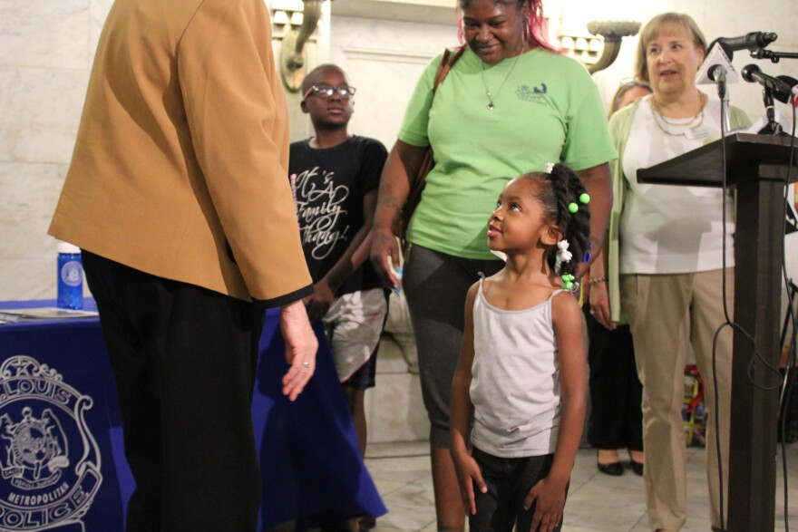 St. Louis Mayor Lyda Krewson stops to meet a family that got a free gun lock at the event at City Hall on June 21, 2017