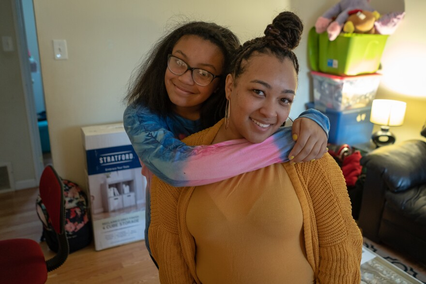 Lauryn Foster hugs her mom, Alesia, in a two-bedroom apartment they share with her grandmother in Maplewood so she can attend MRH schools. Alesia is hoping to move out next year but may not be able to afford an apartment in the district.