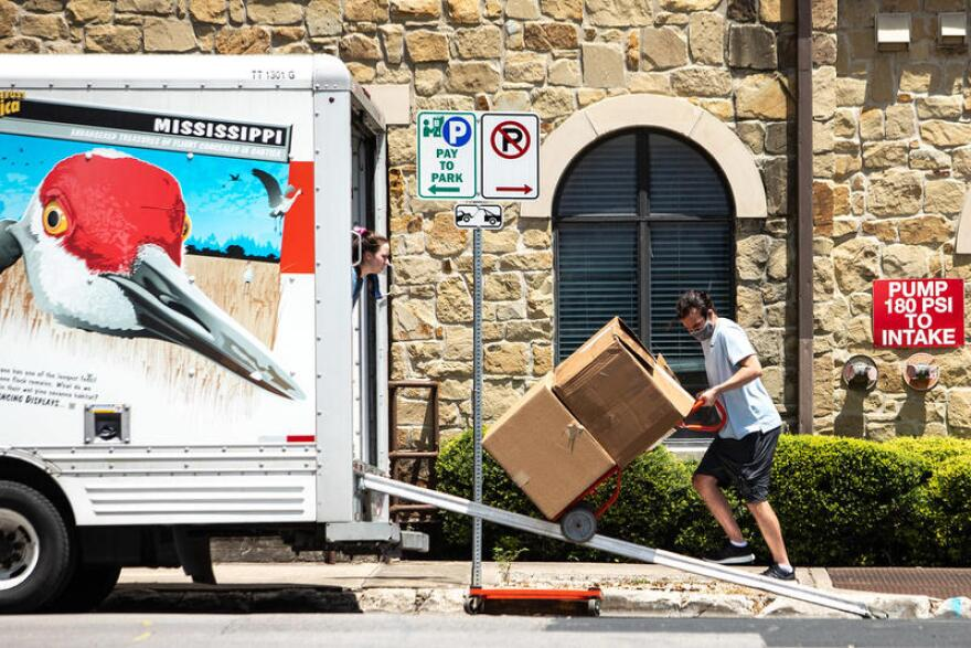 Photo of man unloading boxes from a U-hull truck on a dolly on the UT-Austin campus.