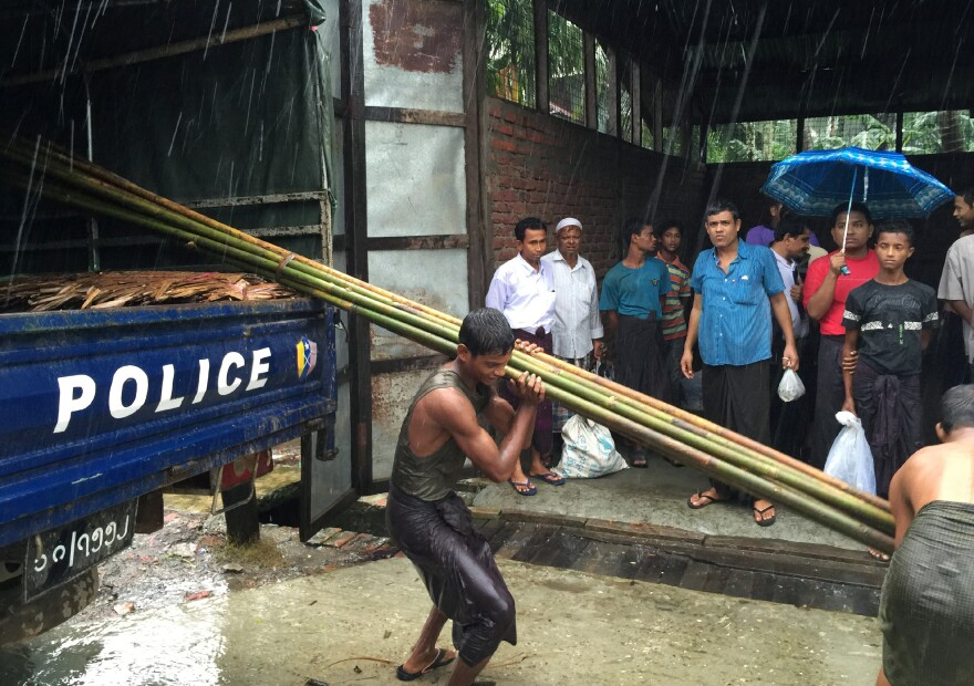 Rohingya residents unload bamboo and supplies from a police truck in Aung Mingalar. Rohingya are not allowed into the city so they must travel to the internment camps outside town, under police escort, to get supplies and medical treatment.