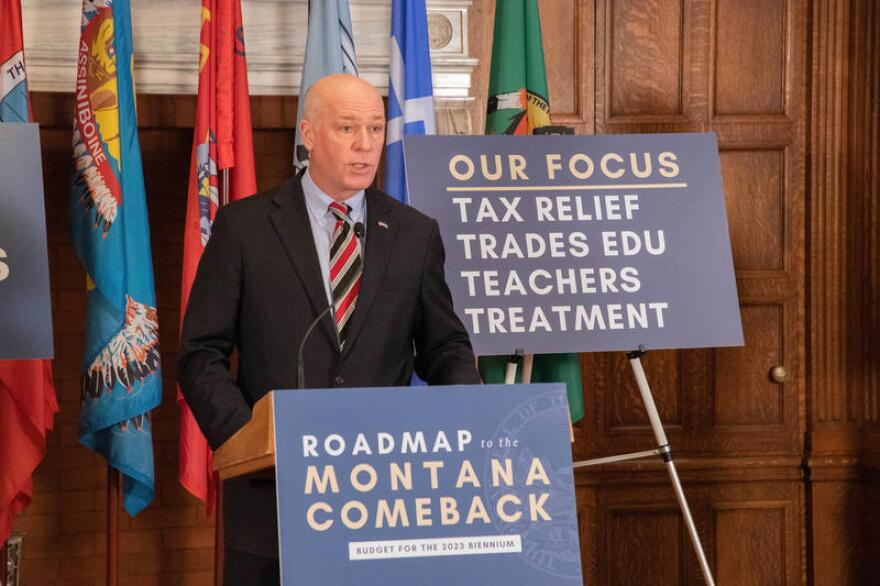 """Greg Gianforte stands at a podium with a poster that reads """"Roadmap to the Montane Comeback: Budget for the 2023 biennium."""""""