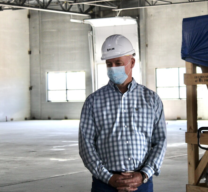Montana Congressman Greg Gianforte stands in a warehouse wearing a blue medical face mask and white hard hat, hands clasped in front of his torso.